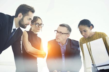 マーケティングの社会のための効果的な広告戦略を議論する開発者の若い乗組員の作業を分析熟練した男性のビジネス コーチ