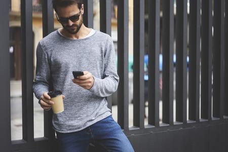 現代のスマート フォンを使用して正しい方向を見つけるオンライン ナビゲーターを使用して移動するハンサムなのひげを生やした男とコーヒーの街 写真素材