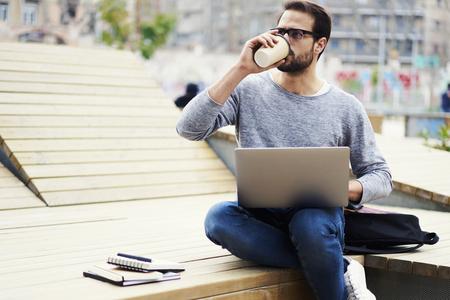 屋外時間でクライアントのタスクを満たすためにしようとしているコーヒーを飲みながら休憩なしで働く若い男性熟練したフリーランサー