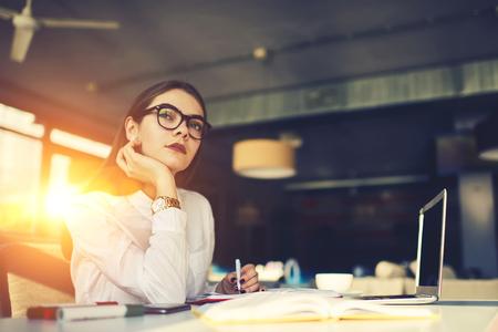 Creatieve vrouwelijke journalist geconcentreerd op het schrijven van een persbericht te wachten op inspiratie verzamelen samen nieuwsverhalen die dat wel zullen doen Stockfoto