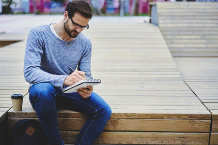 Handsome young male international student preparing homework task creative concept for own business startup project Stock Photo