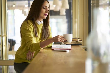 ビジネス会議のための準備作業の休憩中に好きなコーヒーを飲みながらカフェで休んで集中若い女性室長 写真素材