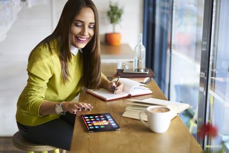 オンライン ポーカーをプレーしながら投資家との会合を待っているカフェでの自由時間を費やしてレストラン ビジネスの魅力的な女性経営者 写真素材