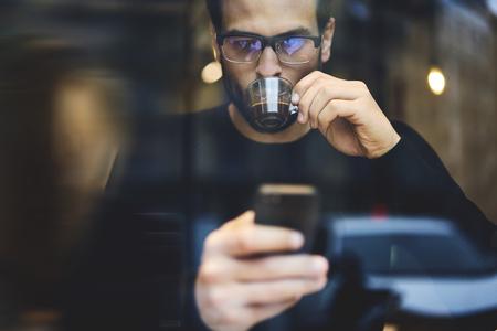 昼休みオンライン チャットを通じてクライアントと通信しながらコーヒーを飲んで休んで集中男性フリーランサーの肖像画 写真素材