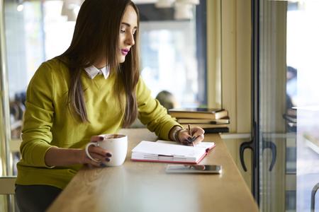 ビジネス企業のアイデアや操作のチェックリストを作るコーヒーのカップで再作成の魅力的な女性経営者 写真素材