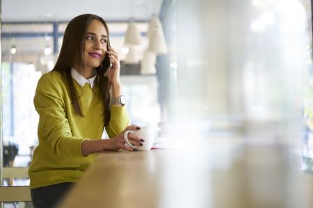 仕事のイベントの手配についての最新ニュースを共有の親友と電話での会話を持つ流行の服に身を包んだ若い女性