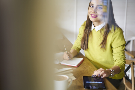 Wifi に接続されている現代のタッチパッドを介してニュースを読んでインターネット上で情報を検索宿題タスクを作成する陽気な女性の魅力的な留学
