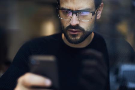 Portret van knappe mannelijke administratieve manager van bedrijfscorporatie die bericht op smartphone controleren