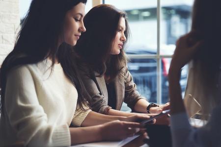 広告キャンペーンを作成するクライアントのタスクを果たす中の共同作業の非公式会合を持つ創造的な女性フリーランサーのグループ