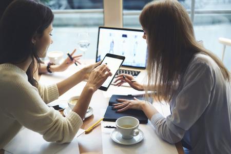 Ervaren vrouwelijke stagiair IT-ontwikkelaars testen applicatie voor online winkelen en bieden snelle toegang tot de webwinkel op d Stockfoto