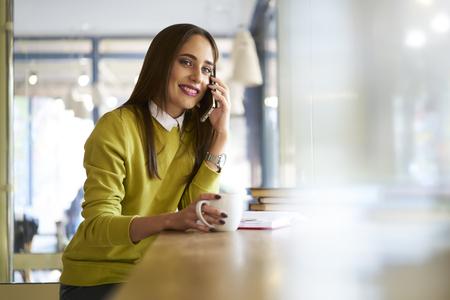 陽気な若いフリーランス メディア マーケティング株式会社モバイルで会話を持つコラボレーション詳細を議論する顧客を引き付けるために広告キャ 写真素材