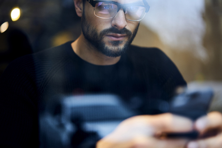 Confident bearded guy freelancer using smartphone connected to wireless internet to search job offers and vacancies on websites Stock Photo