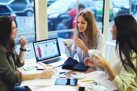 コーヒーを飲むと、現代装置を使用している間ニュースを共有の稼働日後友好的な会談を楽しむ陽気な魅力的な若い女の子