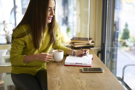 それの熟練した魅力的な女性研修生会社コーディング中で練習をする教科書とウェブサイトのチェック リストを作る