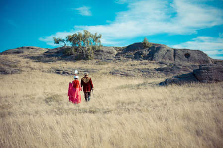 man and woman in kazakh national costume in the steppe