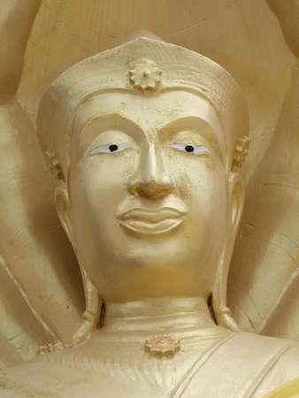 idolatry: Face of a golden Buddha with painted eyes at Pattaya, Thailand (Phra Tmanak Hill - Khao Phra Bat Temple
