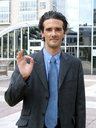 Young businessman making an ok sign with his fingers Stock Photo