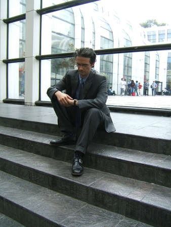 Man waiting sitting on stairs and looking at his watch photo