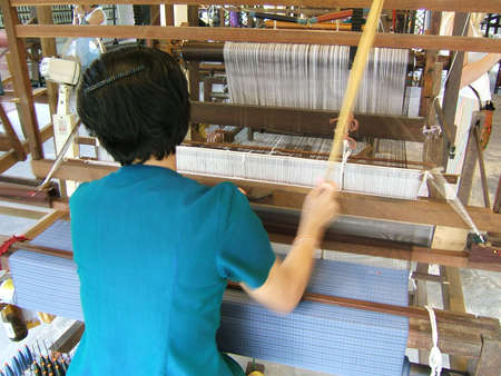 fabricate: Woman working in a traditional handloom waeving Stock Photo