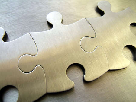 Three metallic jigsaw pieces on a steel background Stock Photo - 294879