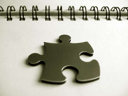 managed: Jigsaw pice on a notebook Stock Photo
