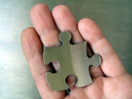 graphicals: Metal jigsaw in human hand Stock Photo