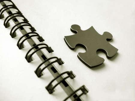Metallic jigsaw on an office notebook photo