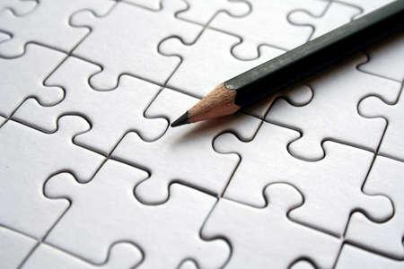 Black pencil on white jigsaws background Stock Photo