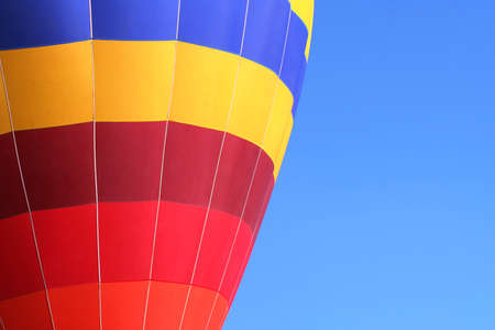 Colorful hot air balloon flying on a blue sky photo
