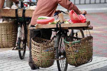 Asian street fruit retailer with bicycle