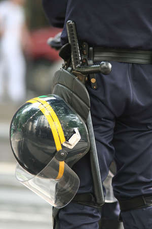 Helmet and truncheon on a police officer in the street
