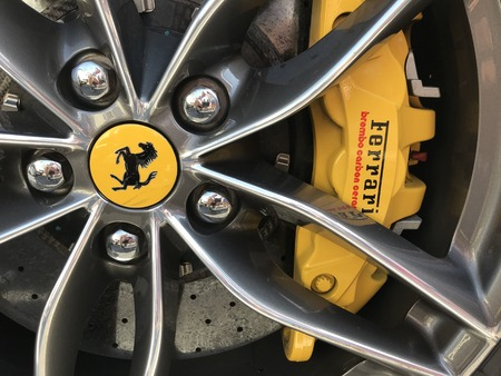 Marbella, Spain - August 10, 2018: Part of a red Ferrari parked inside the famous Puerto Banus. Luxury port where you can take a walk, have a drink and see large and luxurious yachts Editorial