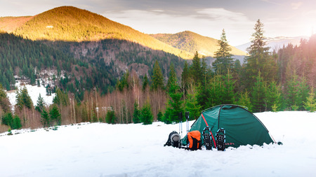 Tent. backpacks. trekking poles, snowshoes on snow in the mountains