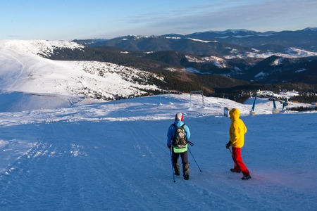 two tourists hiking in winter snowy mountains
