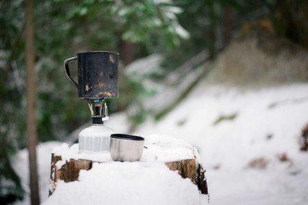 preparing food with a portable gas burner in a winter forest. hunting and hiking concept Stock Photo