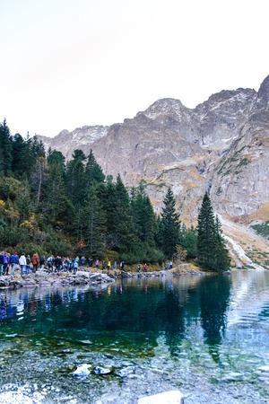 MORSKE OKO, Poland -October 16, 2017: a group of unrecognizable tourists on the shore of the lake sea eye, Tatra Mountains near Zakopane