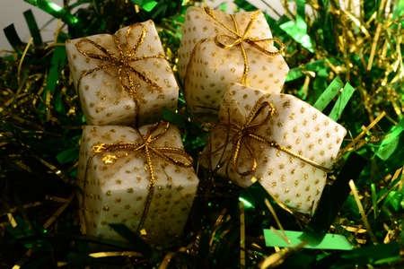 Four white and gold Christmas presents on green tinsel Stock Photo - 11272397