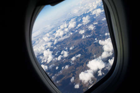 lofty: View from the cabin window looking down on a harsh land and clouds
