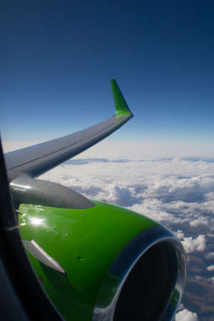 vortices: View of wing and engine in flight over clouds