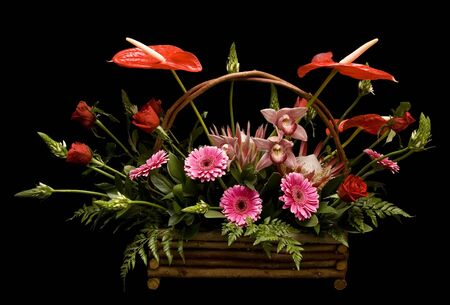 Floral arrangement with assorted flowers in a basket on black background photo