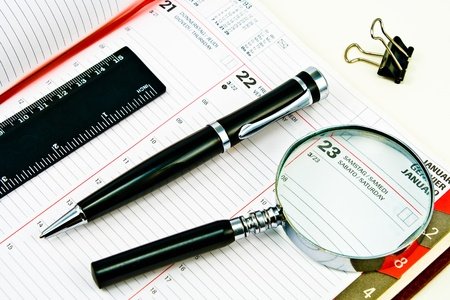 Pen and Agenda with a various tools of punctuality