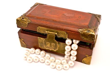 Wooden chest with pearls isolated on white photo