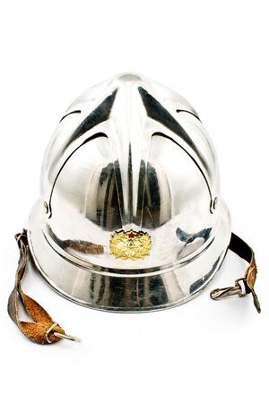 Old firemans metallic helmet isolated on white photo