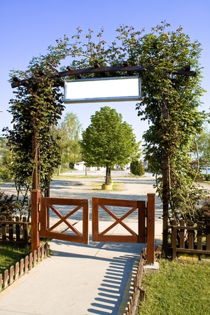 entrance arbor: Green floral arch gate over blue sky Stock Photo