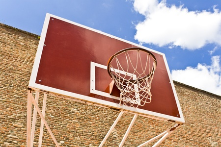 Red basketball board over brick wall and blue sky photo