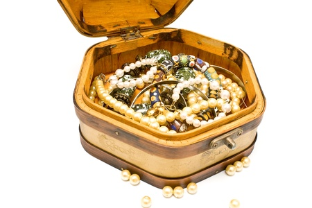 Wooden treasure chest with jewelry isolated on white photo