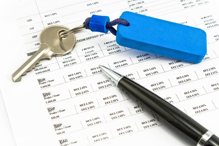 Pen, House key and Interest rates on bank loans on white photo