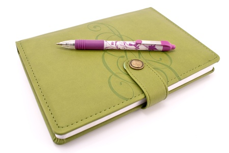 Pen and green notebook isolated on white photo