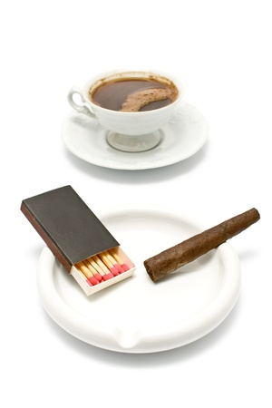 Cigar with matches and cup of coffee on white photo