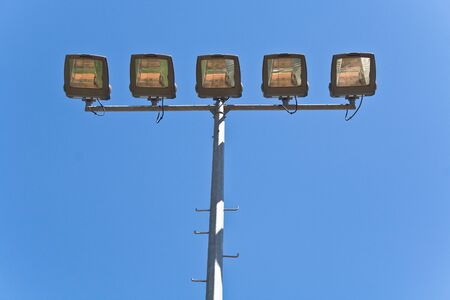 Streetlamps over blue sky with bird on a top photo